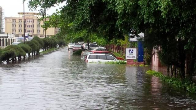 Oyibo man paddles canoe along flooded Lagos street